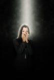 Mujer aterrorizada que se coloca en un haz de la luz blanca Imagen de archivo libre de regalías