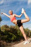 Mujer atlética atractiva joven que estira aptitud fotografía de archivo