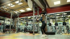 Mujer atlética con el cuerpo de la aptitud que ejercita con la bola de medicina en el gimnasio en el MES lento almacen de metraje de vídeo