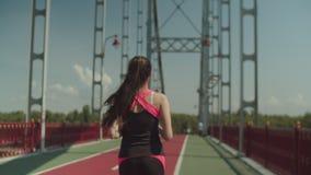 Mujer atlética de la aptitud que activa a lo largo del puente de la ciudad almacen de metraje de vídeo