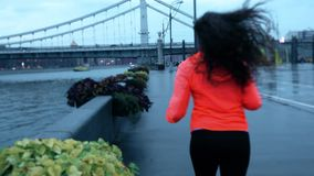 Mujer atlética de la raza mixta joven del tiro de la cámara lenta que corre a lo largo del terraplén del parque de la ciudad por  metrajes