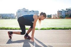 Mujer atlética de la vista lateral en la pista corriente que consigue lista para comenzar el funcionamiento, atleta aficionado Foto de archivo libre de regalías