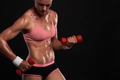 Mujer atlética del culturista con pesas de gimnasia muchacha rubia hermosa con los músculos fotos de archivo libres de regalías