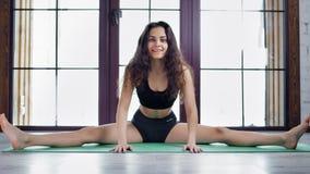 Mujer atlética descalza en la ropa de los deportes que muestra estirar perfecto en la estera gimnástica metrajes