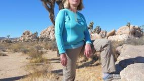 Mujer atlética en el pie en la piedra, panorama de Hat Put His del vaquero ascendente metrajes