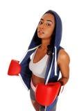 Mujer atlética en guantes de boxeo de la sudadera con capucha que llevan Fotografía de archivo libre de regalías
