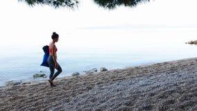 Mujer atlética en paseos de la ropa de deportes en Pebble Beach con la estera de la yoga en bolso metrajes
