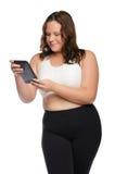 Mujer atlética gorda sonriente con la tableta Foto de archivo libre de regalías