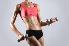 Mujer atlética hermosa que suda mientras que levanta pesas de gimnasia cierre Foto de archivo libre de regalías