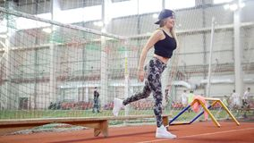 Mujer atlética joven en las polainas que hacen ejercicios de pierna agradables usando un banco almacen de video
