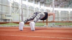 Mujer atlética joven en las polainas que hacen pectorales usando un banco almacen de video