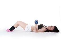 Mujer atlética joven llevando a cabo pesas de gimnasia Imágenes de archivo libres de regalías