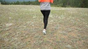 Mujer atlética joven que corre en rastro de montaña El POV sigue la leva Entrenamiento de la puesta del sol en naturaleza Cámara  almacen de metraje de vídeo