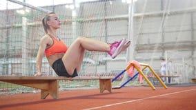 Mujer atlética joven que entrena a su ABS usando un banco almacen de video