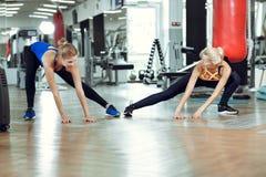 Mujer atlética joven que hace ejercicios con el instructor personal de la aptitud imagen de archivo