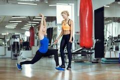 Mujer atlética joven que hace ejercicios con el instructor personal de la aptitud fotos de archivo
