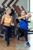 Mujer atlética joven que hace ejercicios con el instructor personal de la aptitud foto de archivo