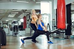 Mujer atlética joven que hace ejercicios con el instructor personal de la aptitud fotos de archivo libres de regalías