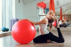 Mujer atlética joven que hace ejercicios con la bola de la aptitud en gimnasio fotos de archivo