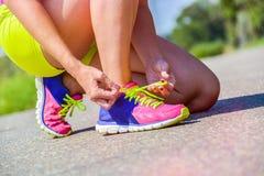 Mujer atlética que ata sus zapatos de los deportes en un día soleado Fotografía de archivo libre de regalías