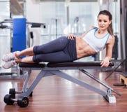 Mujer atlética que descansa sobre un banco en el gimnasio Imagen de archivo