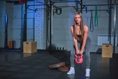 Mujer atlética que ejercita con la campana de la caldera mientras que estando en la posición agazapada Mujer de Bonde que hace en imagen de archivo