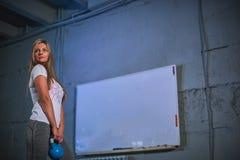 Mujer atlética que ejercita con la campana de la caldera mientras que estando en la posición agazapada Mujer de Bonde que hace en fotografía de archivo libre de regalías