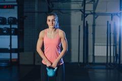 Mujer atlética que ejercita con la campana de la caldera mientras que estando en la posición agazapada Mujer muscular que hace en Foto de archivo