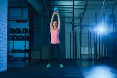Mujer atlética que ejercita con la campana de la caldera mientras que estando en la posición agazapada Mujer muscular que hace en Fotografía de archivo libre de regalías
