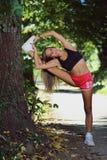 Mujer atlética que estira contra un árbol Fotografía de archivo libre de regalías
