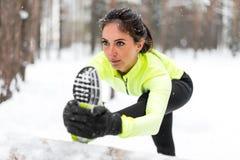 Mujer atlética que estira su tendón de la corva, aptitud del entrenamiento del ejercicio de piernas antes del entrenamiento al ai Imagenes de archivo