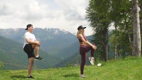 Mujer atlética que hace ejercicio con su socio masculino al aire libre sobre las altas montañas en fondo almacen de metraje de vídeo