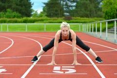 Mujer atlética que hace estiramientos del straddle en pista Fotografía de archivo libre de regalías