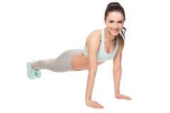 Mujer atlética que hace pectorales en un fondo blanco Modelo de la aptitud con un cuerpo hermoso, atlético Imagenes de archivo