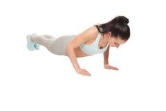 Mujer atlética que hace pectorales en un fondo blanco Modelo de la aptitud con un cuerpo hermoso, atlético Fotos de archivo libres de regalías