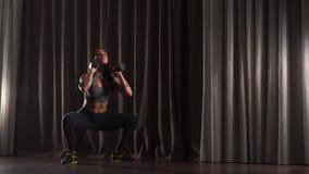 Mujer atlética que hace posiciones en cuclillas con pesas de gimnasia almacen de video