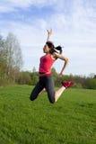 Mujer atlética que salta en el parque Fotos de archivo