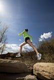 Mujer atlética que salta mientras que activa Imagenes de archivo