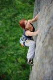 Mujer atlética que sube la pared del acantilado escarpado en tiempo de verano foto de archivo libre de regalías
