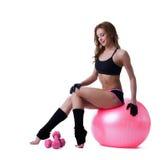 Mujer atlética sonriente que se sienta en bola de la aptitud Fotos de archivo libres de regalías