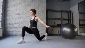 Mujer atl?tica joven de la estera de la yoga que estira la cadera, m?sculos del tend?n de la corva, m?sculos de la pierna dentro  almacen de video