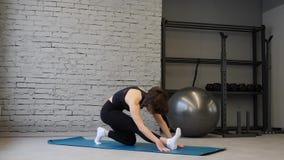 Mujer atl?tica joven de la estera de la yoga que estira la cadera, m?sculos del tend?n de la corva, m?sculos de la pierna dentro  metrajes