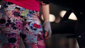 Mujer atlética que camina en una rueda de ardilla en polainas del deporte Primer de piernas en ropa del deporte almacen de video
