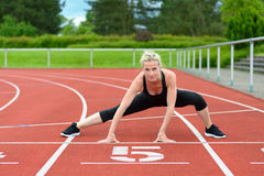Mujer atlética que hace estiramientos del straddle en pista Imagen de archivo libre de regalías