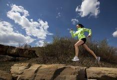 Mujer atlética que salta mientras que se ejecuta Fotografía de archivo libre de regalías