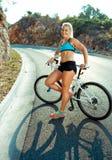 Mujer atlética que se coloca cerca de su bicicleta en un camino de la montaña Fotos de archivo