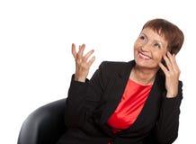 Mujer atractiva 50 años con un teléfono móvil Imagen de archivo libre de regalías