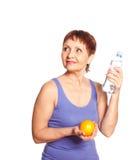 Mujer atractiva 50 años con una naranja y una botella de agua Foto de archivo libre de regalías