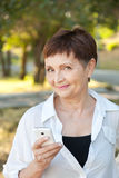 Mujer atractiva 50 años en el parque con un teléfono móvil Fotos de archivo libres de regalías