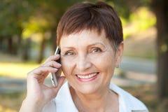 Mujer atractiva 50 años en el parque con un teléfono móvil Imagen de archivo